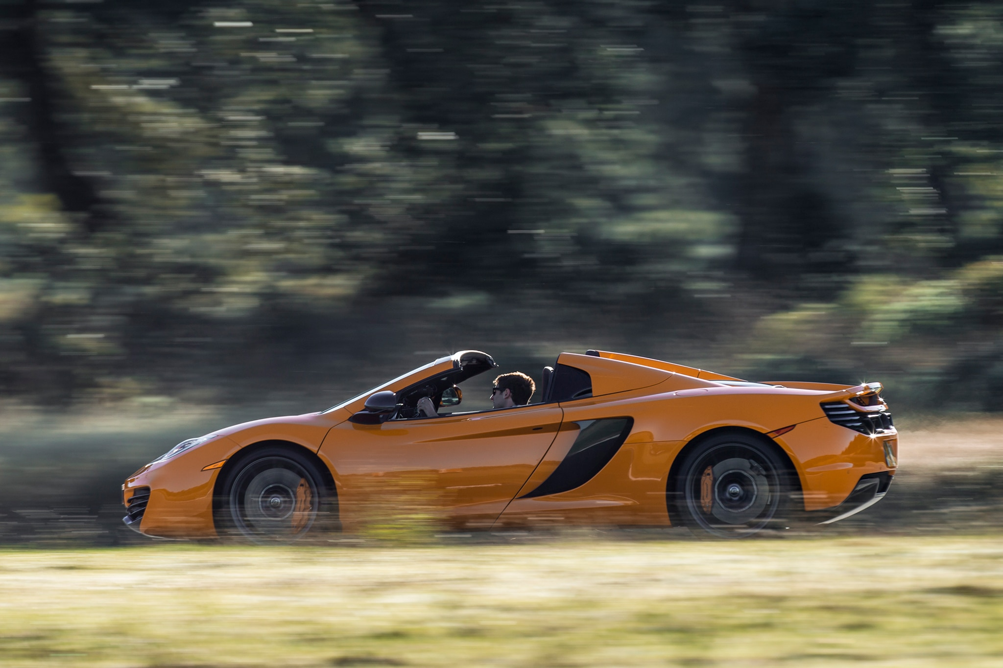 2013 McLaren 12C Spider Profile Drivers Side View In Motion Open1