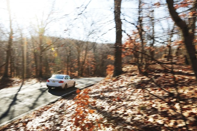 2014 BMW M235i rear three quarter in motion 03