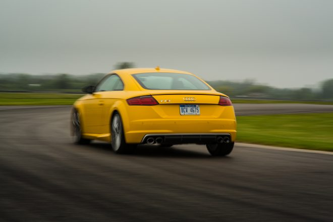 2016 Audi TTS coupe rear three quarter in motion 01